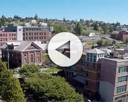 Photo depicting an overhead view of the UW Tacoma campus on a sunny day. There is a 'play' icon overlay indicating there is a video associated with this image.