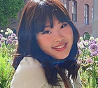 UW Tacoma student Seonhwa Pak in front of a planter full of flowers.