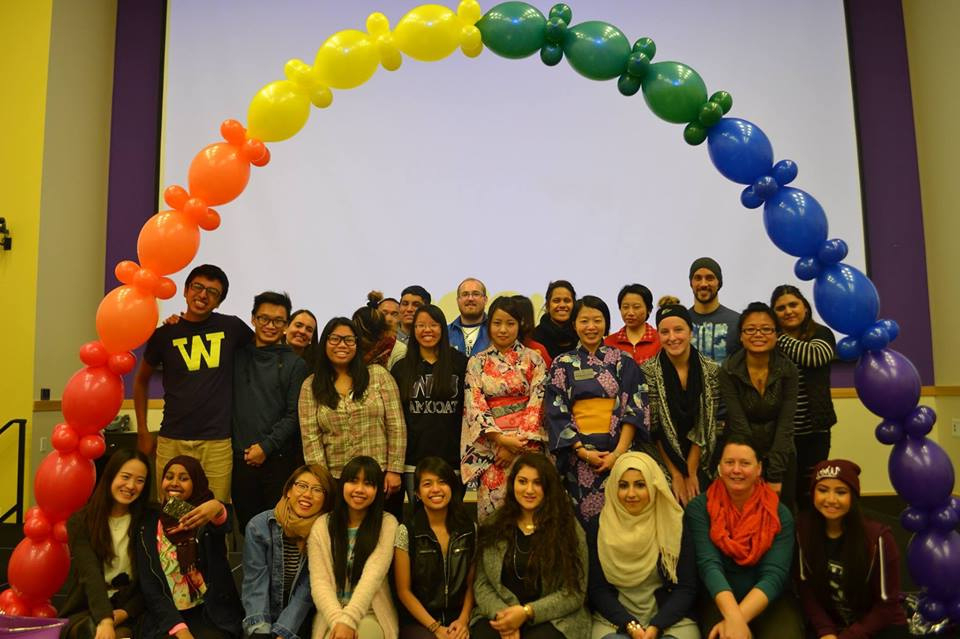Photo depicting 26 students posing under a rainbow-colored arch made of inflated balloons.
