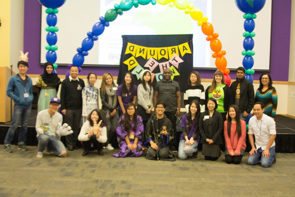 Photo depicting 20 students posing under a rainbow-colored arch made of inflated balloons. In the background is a sign that reads Around the World